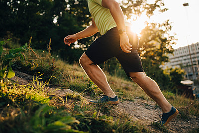 Low section of male athlete running on land - p426m2270579 by Maskot