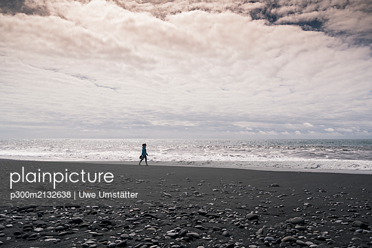 Young woman walking on barefoot on a lava beach in Iceland - p300m2132638 by Uwe Umstätter