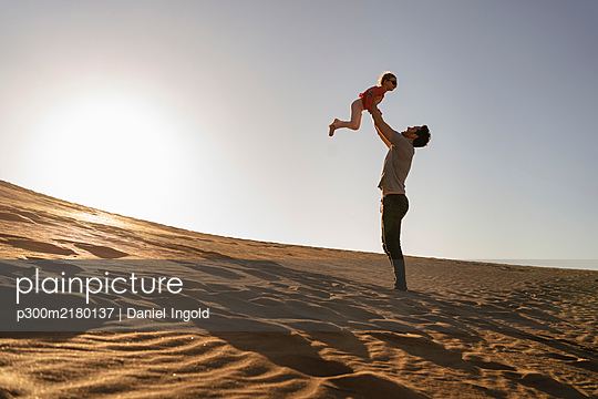 Father playing with daughter in sand dune at sunset, Gran Canaria, Spain - p300m2180137 by Daniel Ingold