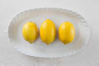 Drei Zitronen auf Servierteller - p1149m1092672 von Yvonne Röder