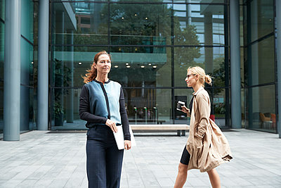 Mature woman standing and holding laptop with colleague walking in background against office building - p300m2227077 by Pete Muller
