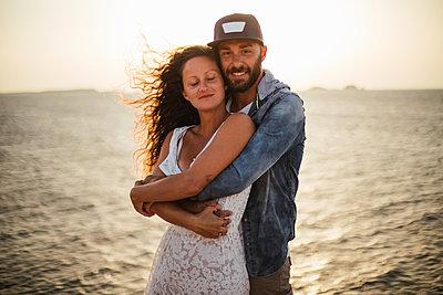 Romantic couple hugging on coast, portrait, Santa Teresa Gallura, Sardinia, Italy - p429m2077982 by Guido Cavallini
