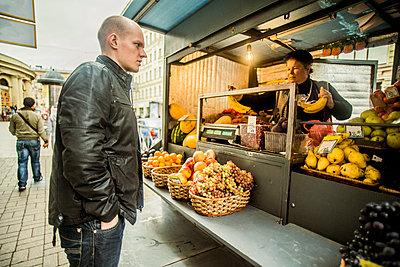 Caucasian man buying produce at fruit kiosk - p555m1413200 by Aleksander Rubtsov