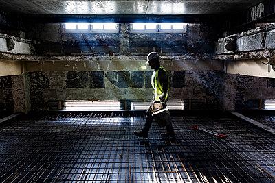 Bauarbeiter trägt seine Ausrüstung auf eine Baustelle trägt - p590m2031576 von Philippe Dureuil