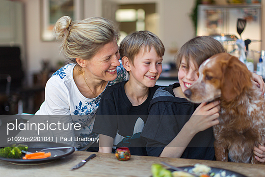Happy mother and sons with dog at dinner table - p1023m2201041 by Paul Bradbury