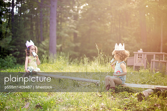 Girls playing telephone on wooden log in garden - p555m1409487 by Shestock