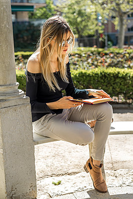 Young woman with notebook sitting on bench - p300m1581186 von VITTA GALLERY