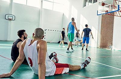 Basketball players during break, sitting on court - p300m1587453 von Zeljko Dangubic