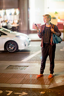 Mature woman texting on smartphone in the street at night, London, UK - p429m999607 by dotdotred