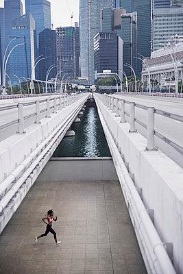 Mixed Race woman running under urban bridge - p555m1301940 by Hello Lovely