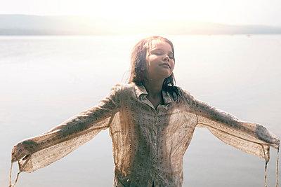 Caucasian girl wearing wet shirt near sunny lake - p555m1531622 by Vladimir Serov