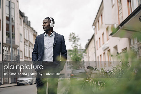 Young businessman listening music with headphones walking along the street - p300m2166753 by Kniel Synnatzschke