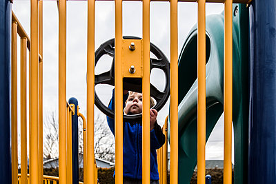 Toddler on playground looking curiously at play steering wheel - p1166m2129436 by Cavan Images