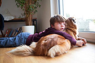 Kind kuschelt mit Hund - p1308m2301262 von felice douglas