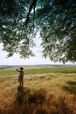 Woman standing under a large tree,  looking out onto a gently sloping landscape. - p1433m1589997 by Wolf Kettler