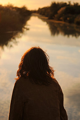 Young woman looking at river at sunset - p1468m1539315 by Philippe Leroux