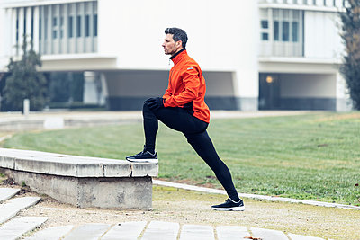 Determined male athlete doing stretching exercise at park - p300m2275559 by Josep Suria