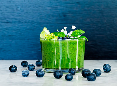 Blueberries and green smoothie - p312m1139739 by Peter Rutherhagen