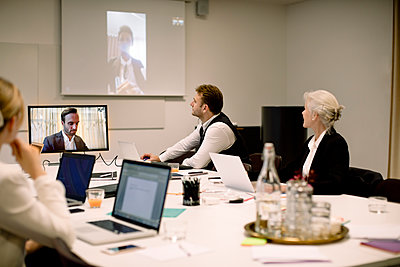 Male and female business professionals discussing in global video conference at board room - p426m2187233 by Maskot