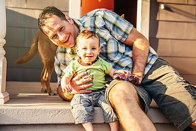 Caucasian father and son sitting on patio - p555m1306264 by Inti St Clair photography