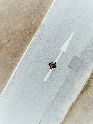 Man walking on country road with directional arrow, aerial view - p586m1088329 by Kniel Synnatzschke
