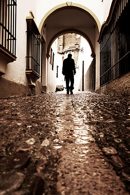 Rearview man walking up old street in Ronda, Spain - p597m2063516 by Tim Robinson