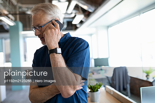 Portrait of senior business owner on cell phone in office - p1192m2123288 by Hero Images