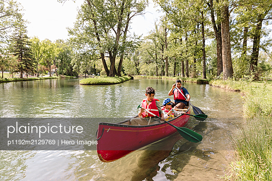 Father canoeing with two sons on lake in park - p1192m2129769 by Hero Images