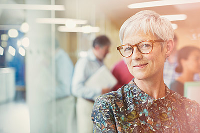 Portrait smiling senior businesswoman in office - p1023m1086291f by Sam Edwards