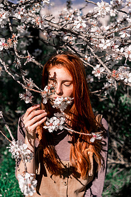 Redheaded woman smelling tree blossoms - p300m2083097 by VITTA GALLERY
