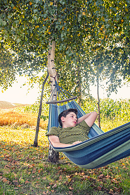 Boy lying in hammock - p879m2257746 by nico