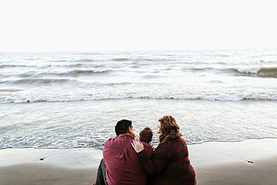 Rear view of mother and father sitting on beach - p924m1224903 by Jennifer van Son