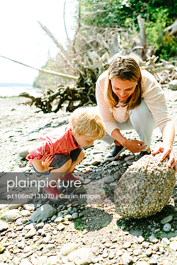 Mother and son on a rocky beach looking in tide pools on a sunny day - p1166m2131370 by Cavan Images