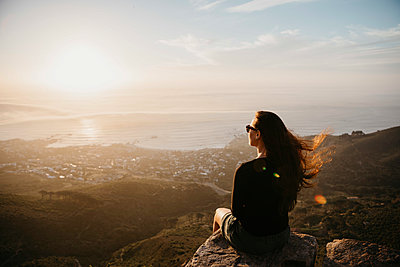 South Africa, Cape Town, Kloof Nek, woman sitting on rock at sunset - p300m2081036 by letizia haessig photography