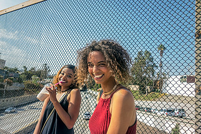 Cheerful young women enjoying sunny day while standing on bridge - p300m2239993 by LOUIS CHRISTIAN
