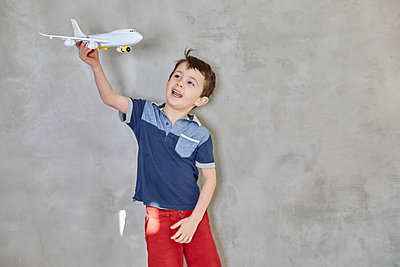 Boy playing with model airplane while standing against gray wall - p301m1579649 by Liesel Bockl