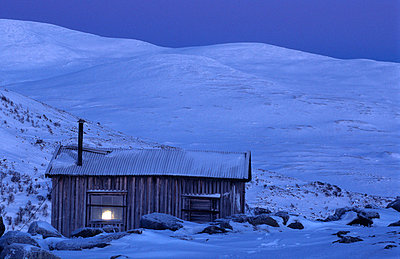 Remote log cabin at dusk - p5756072f by Svensson, Mikael