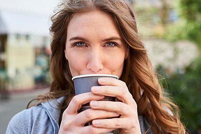Frau trinkt Kaffee zum mitnehmen aus Pappbecher - p890m1440017 von Mielek