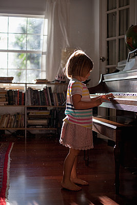 Girl standing playing old piano at home - p924m1446950 by Kinzie Riehm