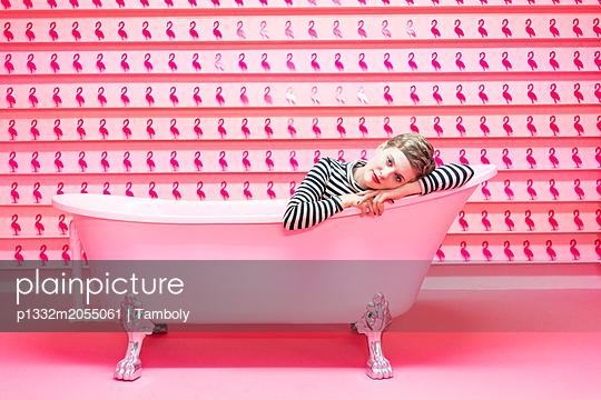 Frau liegt in Badewanne vor pinkfarbenem Hintergrund - p1332m2055061 von Tamboly