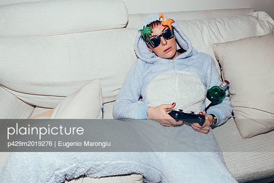 Woman wearing adult bodysuit holding games controller - p429m2019276 by Eugenio Marongiu