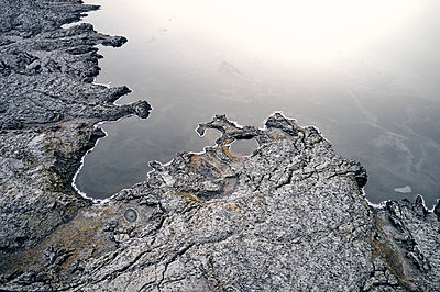 Calm water near eroded shore - p1166m2163044 by Cavan Images