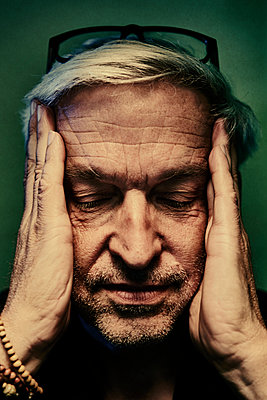 Mature man with closed eyes and hands on his head, portrait - p1312m2237635 by Axel Killian
