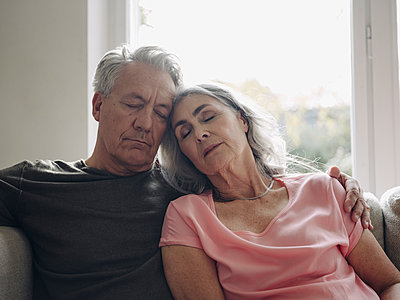 Senior couple napping on couch at home - p300m2156203 by Gustafsson