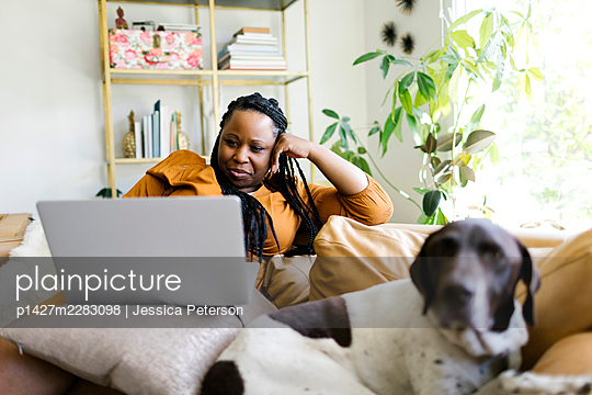 Woman lying on sofa with dog and working on laptop - p1427m2283098 by Jessica Peterson