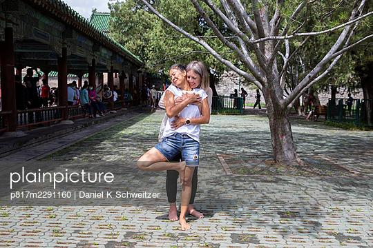 China, Peking, Himmelstempel, Zwei Frauen umarmen sich - p817m2291160 von Daniel K Schweitzer