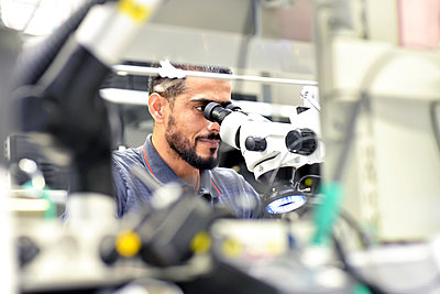 Man using a microscope for the quality control in the manufacturing of circuit boards for the electronics industry - p300m2081117 by lyzs