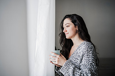 Thoughtful smiling woman holding coffee cup while looking through window at home - p300m2265657 by Eva Blanco