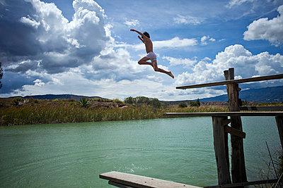 A young boy jumping into a lake - p30120592f by Alejandro Nino