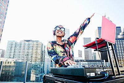 Smiling Black DJ on urban rooftop - p555m1301710 by Peathegee Inc